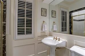 """BEDROOM # 3 WITH PRIVATE BATH – 13' X 16' 2"""": Tall divided-light windows; Multi-piece crown molding; Recessed lighting; Hardwood floor; Two  Closets: (Each  4' 2"""" x 22""""); Private Bath: Pedestal sink; Mirrored wall; Corner shower with marble tile surround, inlaid contrast tile border & glass door; Toilet; Built-in linen cabinet; Window with plantation shutters; Recessed lighting; Chair rail with wainscoting; Diagonal 12"""" x 12"""" marble tile floor inlaid with contrasting marble acc"""