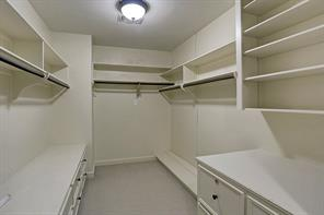 """MUD ROOM – 5' 10' X 11' 2"""": Stainless steel sink set into slab granite counter; wall-mounted cabinets with top-of-cabinet display space; Built in bench seat (5' 7"""" long) with storage drawers, upper level shelf, coat and accessory hooks; Shelf tower with storage cubbies, Storage closet (3' 7"""" x 14"""");Ceiling-mounted rail lighting with adjustable and repositionable lamps; Hardwood floor; Exit door with upper level divided-light glass panels leads to covered walkway to Garage"""