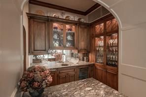 Bar - The fully-equipped bar connects to the dining room and kitchen and serves as a butler's pantry. Amenities include a chiller, ice maker, leaded-glass-front cabinets, honed granite countertops, hammered brass sink and smoked-mirror backsplash.