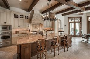 Kitchen - The Kitchen features a honed travertine floor; large island with pull-up seating and Fireclay sink; Viking electric oven, cabinet-front SubZero, Asko dishwasher, and Wolf appliances; rich granite countertops and custom chandelier.