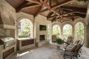 "Loggia - The sheltered outdoor living and dining area features a beam truss ceiling; stone and ""Cedar Bayou Bricks""; raised fireplace; television mount; sink with granite deck; and summer kitchen with grill. Benefit from this custom feature of a separate zone of air conditioning available outdoors for the hot Houston summer months."