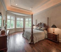 Master Suite 23' x 15' - The serene master bedroom enjoys stunning views of the patio, pool, and bayou through a rear wall of bay windows. Features include a 13-foot tall ceiling with coved lighting and walnut flooring.