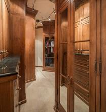 One of Two Custom-fitted Master Closets - Rich paneling and mirrored wardrobes enhance this custom-fitted master closet. A built-in chest-of-drawers has a marble shelf.