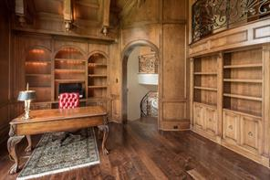 Library 21' x 16' - Stunning library at mezzanine-level has a double-height, elaborately coffered and beamed ceiling with corbels; fireplace with granite surround; lighted book/display cabinets; and a reading loft.
