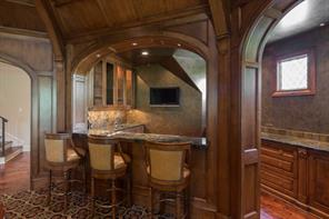 Game Room 29' x 26' - The main staircase landing opens into the game room. Amenities include a superbly carved coffered ceiling; designer carpet; built-in media; and a walk-in fully-equipped bar.