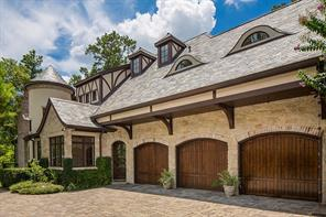 Rear Elevation/ Three-Car Garage -The three-car garage with wood facade doors adjoins a large motor court and gated and paver driveway. ColorFlake garage floor was added to the garage along with plenty of custom closets and shelving for additional storage.