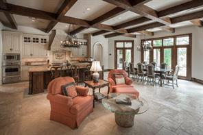 Living Room 27' x 18' - The double-height living room features an apse with tall windows overlooking the pool, patios, and down to Buffalo Bayou. Oversized, double-sided fireplace, shared with adjoining kitchen, has a delicately-carved mantel.