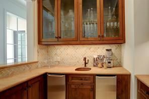 A wonderful WET BAR for entertaining. And handsomely designed with travertine countertops/tile backsplash, refrigerator, ice maker and several glass front cabinets to display glassware.