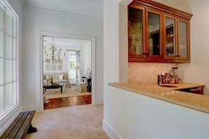 View from the Wet Bar along the Front Entry corridor leading to the formal LIVING ROOM.  Notice the great amount of light entering the hallway from the windows, also allowing views of the the back and side yards.