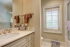 One of several EN SUITE BATHS on the second floor showing the stone countertop with painted cabinets below, stone flooring, shuttered window and tub/shower bath with tile surround.