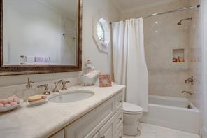 The second Guest Bedroom's EN SUITE BATH  includes  stone tile flooring, stone counter top with painted cabinet/drawers below, tub/shower with stone surround, and charming octagonal window with stone surround.