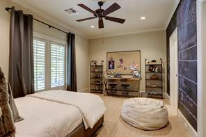 The third  GUEST BEDROOM with its carpeted flooring, painted walls with chalk board wall on one side, ceiling fan and shuttered windows.