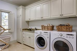 The spacious UTILITY ROOM is located on the second floor and includes a sink with granite counter top/painted cabinet, stone flooring, wall of storage cabinets, shuttered windows.