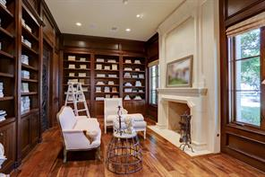 The STUDY (16 X 11) includes wide-plank hardwood flooring, wood paneled walls, gas log fireplace with limestone surround/mantle, built-in shelving, recessed lighting, built-in speakers and expansive mullioned windows overlooking the front yard.