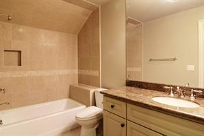 The third floor BATHROOM includes granite countertops, tub/shower with decorative insets and stone flooring.