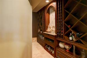 The WINE ROOM is situated just off the Study and features ample bottle storage for the wine enthusiast. Also included is a granite covered countertop, stained wood cabinets and shelving, wine cooler and stone flooring.