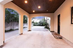 View of the DRIVEWAY and covered PORTE COCHERE with its wood paneled ceiling, recessed lighting, stone steps to the wooden side door to the Kitchen area.