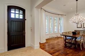 The FRONT ENTRY is beautifully appointed with a stately wood door with mullioned windows above allowing filtered light to enter the space.  Large wide openings lead to the Dining Room on one side and the Study on the other side of the stone floored Entry. A great spatial plan for entertaining!