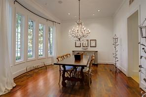 The spacious DINING ROOM (18 X 16) is brightly lit with a series of large windows facing the front yard. The room also features painted walls, crown/base molding and wood plank flooring.
