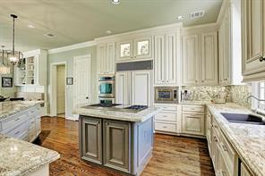 Another view of the kitchen which has an island, appliance garage and large pantry.