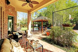 The backyard features a covered patio, gazebo with cafe lights, sport court and mosquito system.