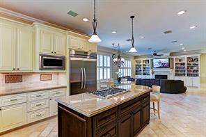The kitchen opens to the breakfast room and family room at the far end of the room. It includes built in bookcases and a gas log fireplace