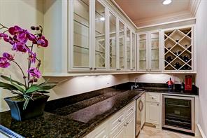 The wet bar behind the stairs with wine storage, built in glass front cabinets, granite counter top and wine chiller
