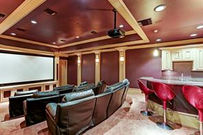 The media room has the feel of a theater with projector, giant screen, comfortable leather seats, and wet bar with refrigerator at the back of room