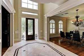 The 2 story entry with inlaid marble floor, beautiful crystal chandelier opens into the study, dining and living rooms