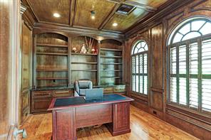 Wood paneling on walls and ceiling of study with wall of built in bookcases, hardwood floors and huge windows