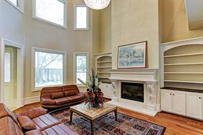 The light filled 2 story living room has a gas log fireplace, built in bookcase, hardwood floor, crystal chandelier, and multiple windows over looking back yard