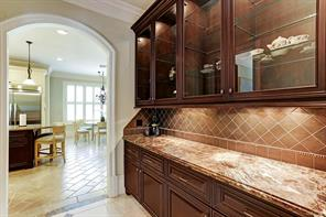 The butler s pantry with glass front cabinets and granite counter top connects the dining room and kitchen.