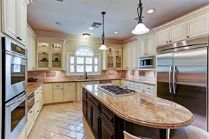 The fabulous chef s kitchen features granite counter tops, stainless Thermador appliances, built in refrigerator and separate freezer, island with breakfast bar, tons of cabinets and custom stone floor