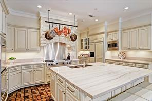 A closer view of the kitchen with butlers pantry beyond and glass cabinetry.