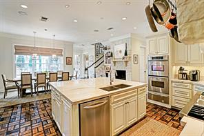 A view of the kitchen and breafast area viewing the yard.  The gameroom is directly past the stairs.  In between the fireplace and stairs is a convenient workstation and cookbook storage.