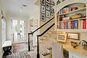 A closer view of secondary stairs, work station and french doors to outdoors.  The entrance to the gameroom is to the right.