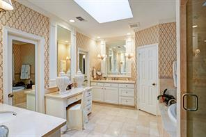 Another view of master bath focusing on dual sinks, separate vanity and closets.