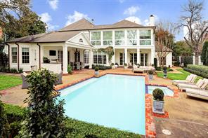 A spectacular view of the outdoors with outdoor kitchen covered loggia, manicured yard and pool with spa!  And STILL plenty of yard!