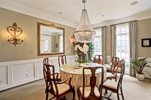 To the right of the entry is the intimate dining room with wood floors, art lighting and and paneled wainscoting.