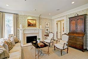To the left of the entry is a wonderful living room with 1 of 3 fireplaces.  This fireplace has a marble surround and wood mantle.  Light and cheery windows, hard wood floors and Schumacher wall paper makes this a great room for conversation.