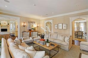 The warm and inviting family room is open to the kitchen, living area and entry.  It has hardwood floor, wood molding and Schumacher Rafia neutral wall covering.  There is also art light and another fireplace not sown in this photo