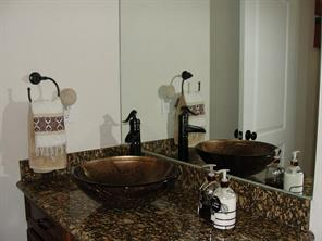 Spacious guest bathroom with granite counter top and glass vessel sink with brushed bronzed faucet