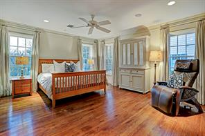 The pretty master bedroom has a multitude of windows allowing abundant natural light. Note the lovely hardwood floors, recessed lighting and so much more.