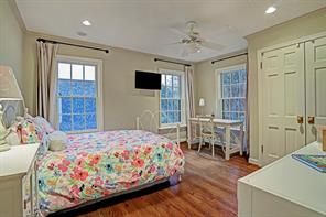 Another spacious bedroom filled with light from it's many windows, pretty wood floors, recessed lighting and a ceiling fan.