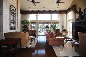 Living room that has gas log fireplace,beautiful wood flooring and vaulted ceiling also opens out through sliding glass doors to another covered patio.  Iron gate above fireplace can stay with the home.