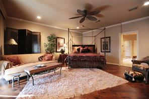 Master bedroom retreat with hand scraped wood flooring and sliding glass doors that open out to patio.