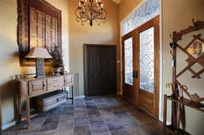 Foyer with stone flooring,venetian plaster walls and chandelier that stays with the property.
