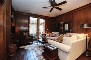 Study with wood panels, plantation shutters and hand scraped wood flooring.