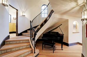CIRCULAR STAIRCASE with hardwood treads, tile risers, and iron railings & balusters.  The railings were made on-site and were custom designed with wrapped ends.  Notice the interesting niche under the staircase - a perfect spot for a Piano!  And the POWDER BATH is conveniently located through the open door on the left.