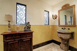 POWDER ROOM with imported 19th century antique European encaustic tile flooring, decorative plaster walls and ceiling, a hand carved Cantera stone vessel sink, hand carved wooden sconces, and a custom-made wall-mounted bronze faucet.  Notice the leaded glass windows and the gracious size of this Powder Bath.